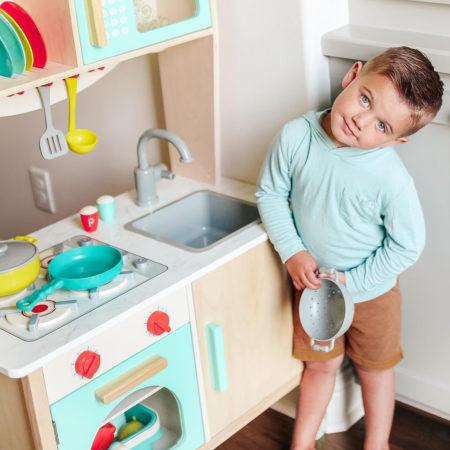 Boy in play kitchen.