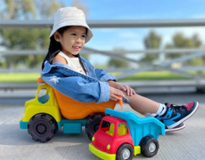 Girl sitting in toy truck.