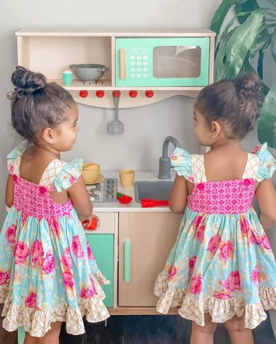 Two girls in play kitchen.