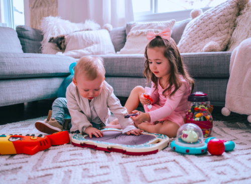 Young girl and baby boy on a living room floor with toys.