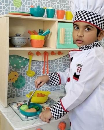 Boy in chef costume in toy kitchen.