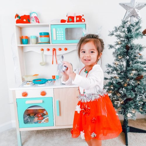 Girl in play kitchen.
