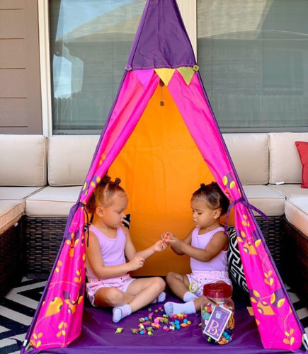 Two young girls in a colorful play tent.