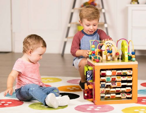 Two kids playing with a wooden activity center.