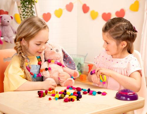 Two girls making DIY jewelry.