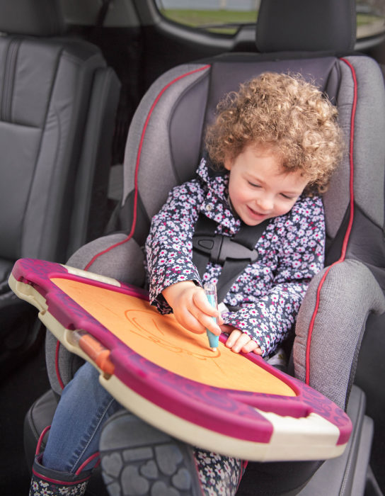 Smiling boy with a drawing board in a car.