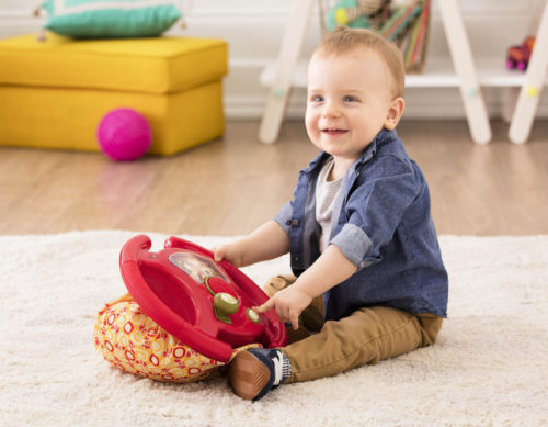 Smiling boy with toy steering wheel.