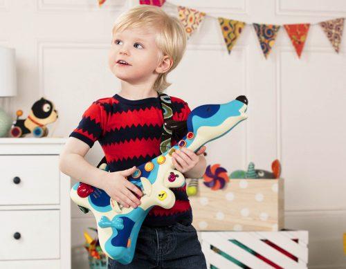 Boy playing a toy guitar.
