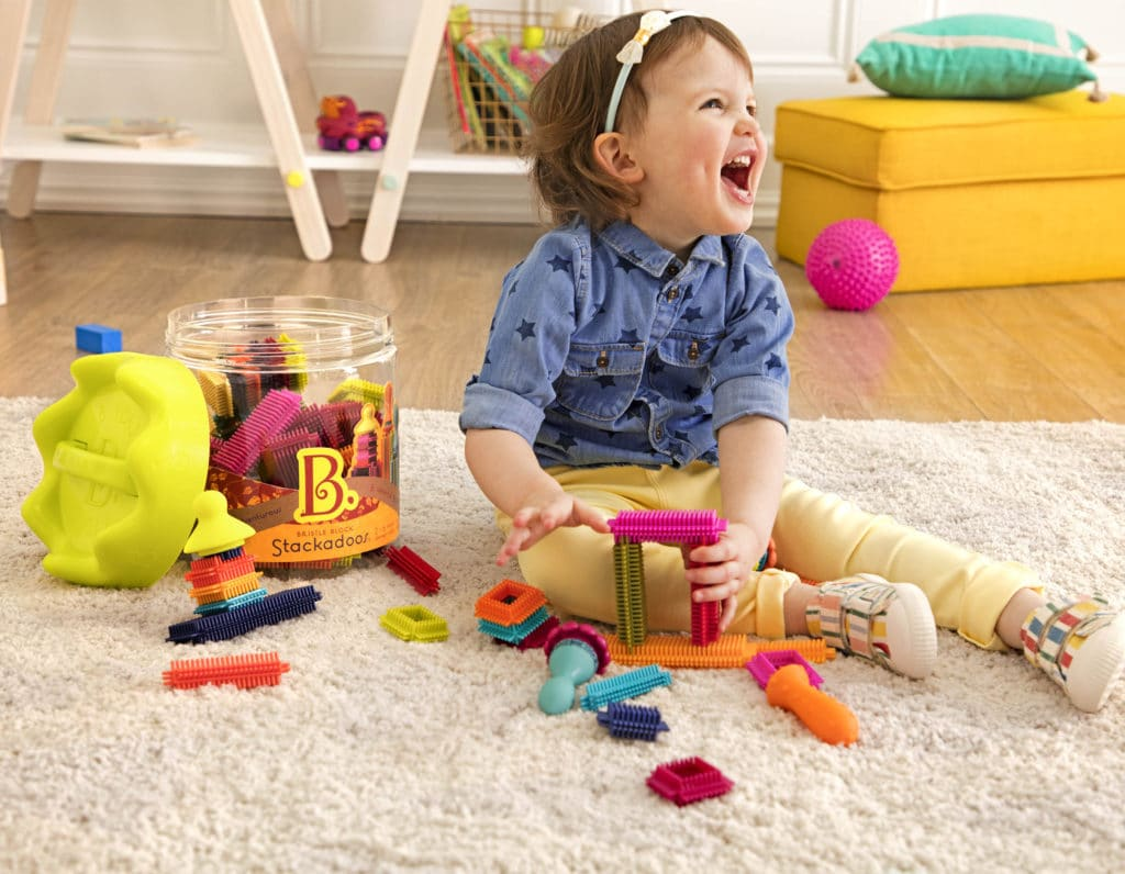 Girl laughing and playing with colorful bristle blocks on the floor.