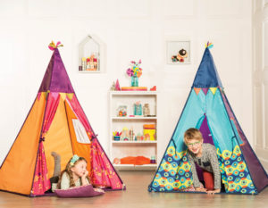Girl lying down in an orange play teepee and boy crawling out of a blue play teepee.
