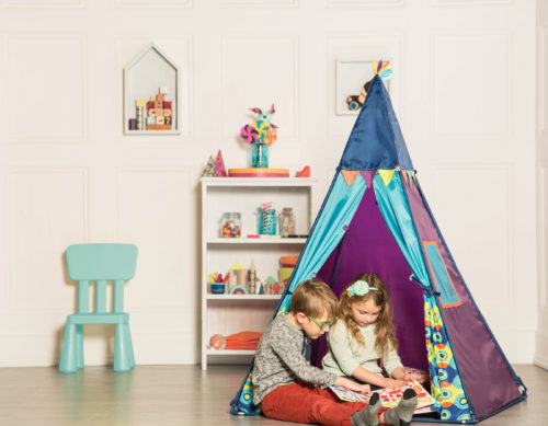 A boy and a girl in an indoor tent.