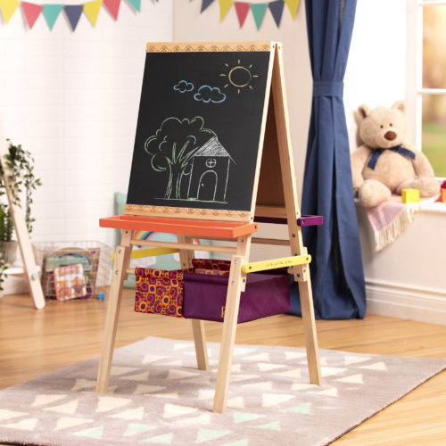 Kids easel with a drawing of a house with trees and sky on it.