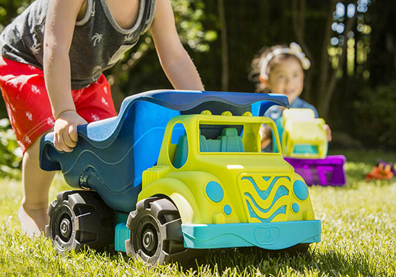 Child pushing a large and colorful toy dump truck.