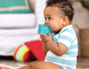 Baby nibbling on a blue baby block.