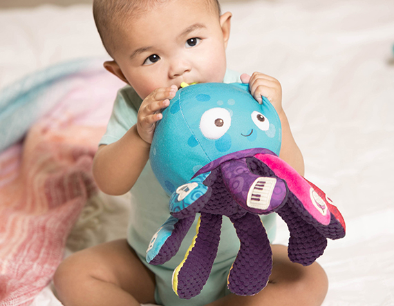 Baby holding on to a plush octopus toy.