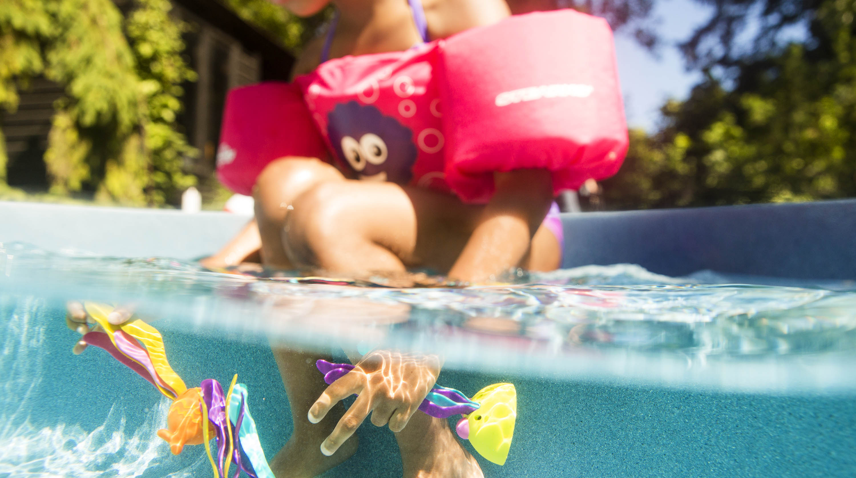 Girl reaching into the pool for sinking toys.