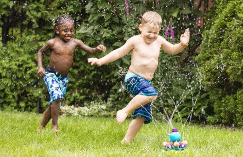 Two boys running around a sprinkler.