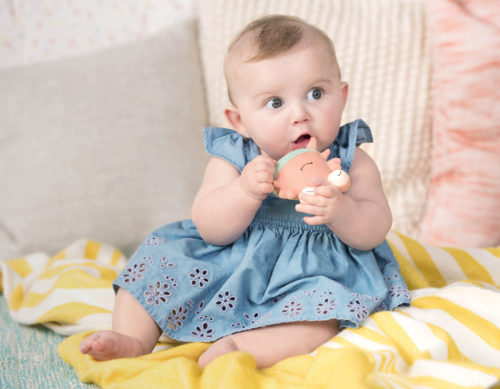 Baby girl with a crab teether.