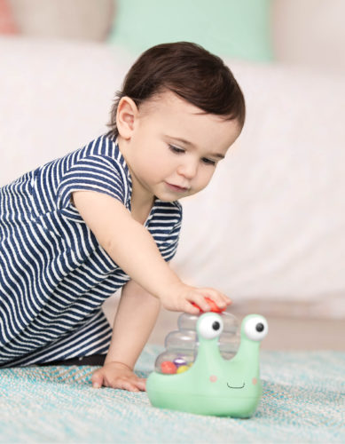 Baby pushing on a snail ball popper toy.