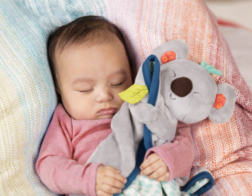 Sleeping baby cuddling a plush koala blanket.