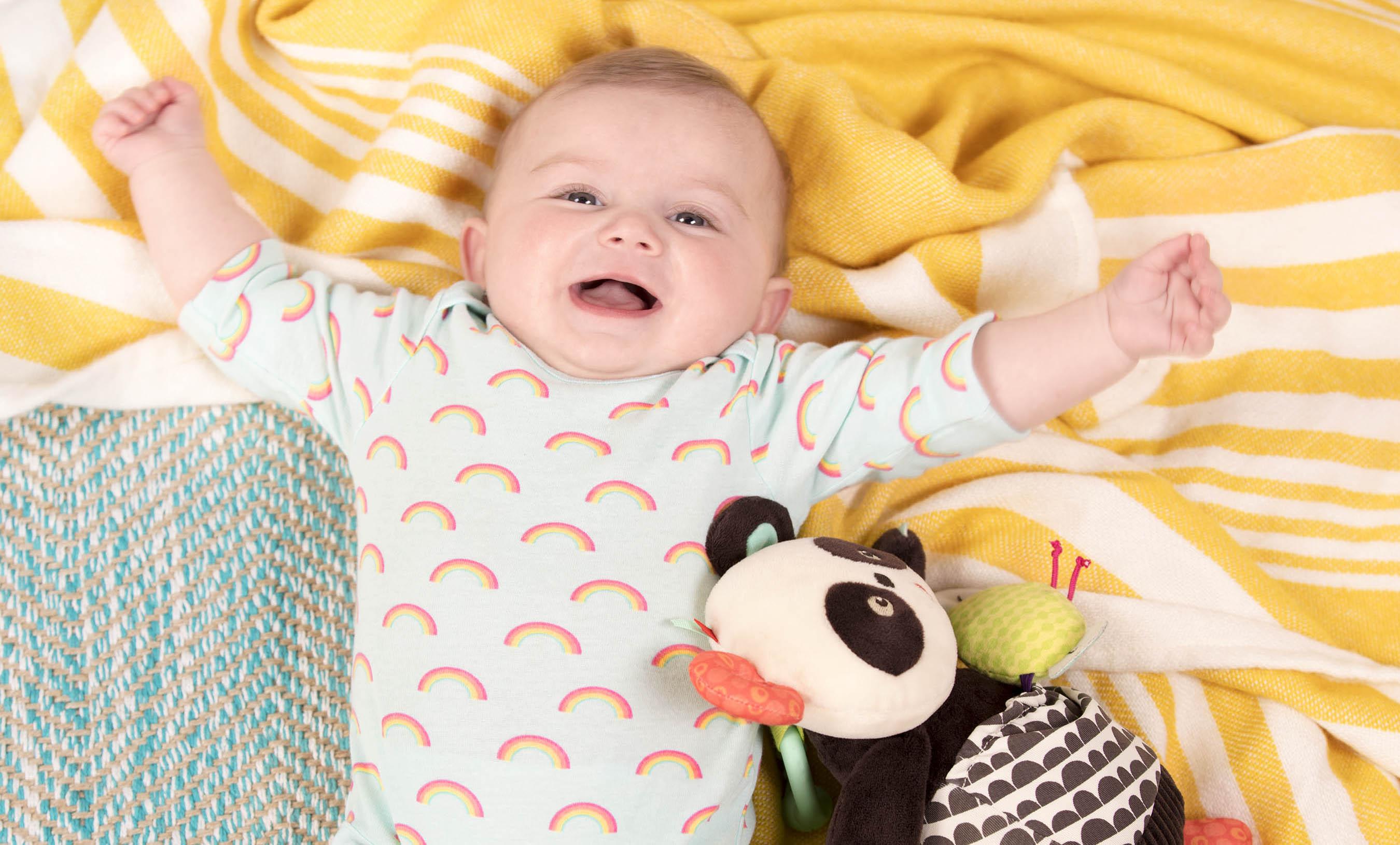 Smiling baby with plush panda.