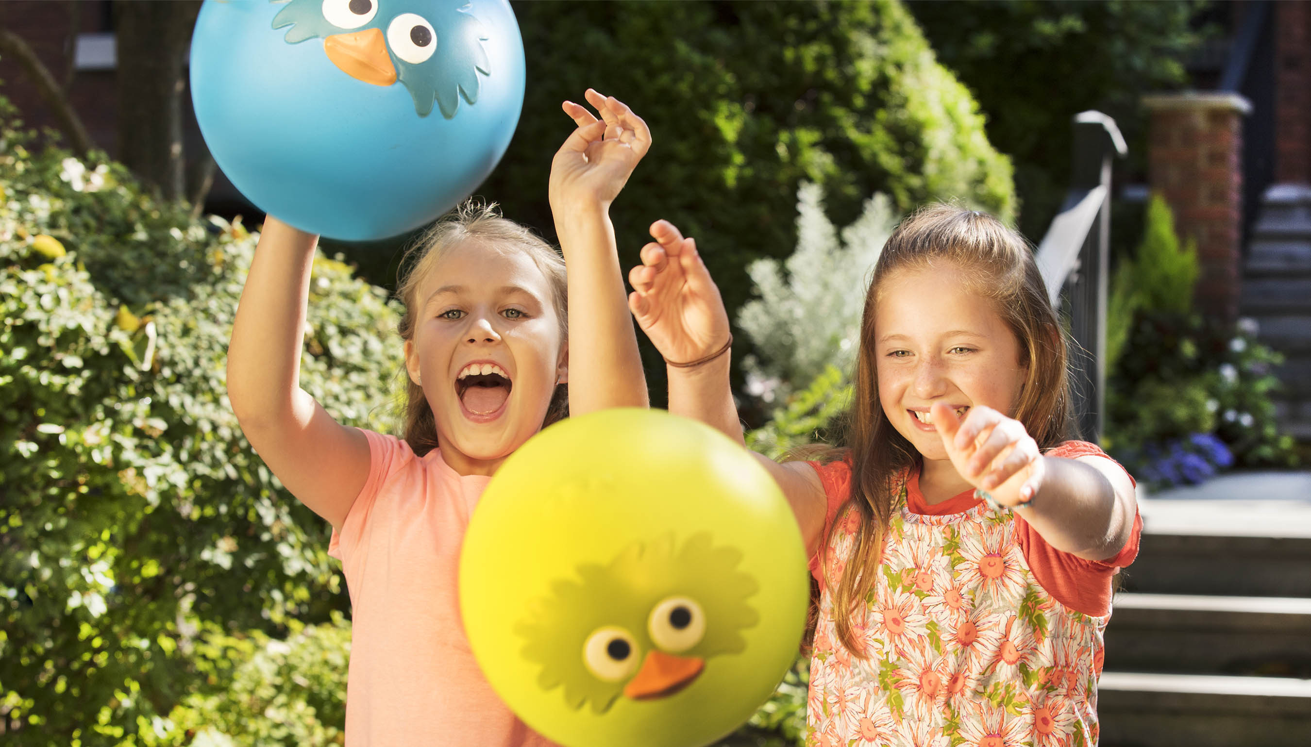 Two smiling girls playing with bird-inspired bouncy balls.