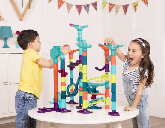 Boy and girl playing with a marble run toy.