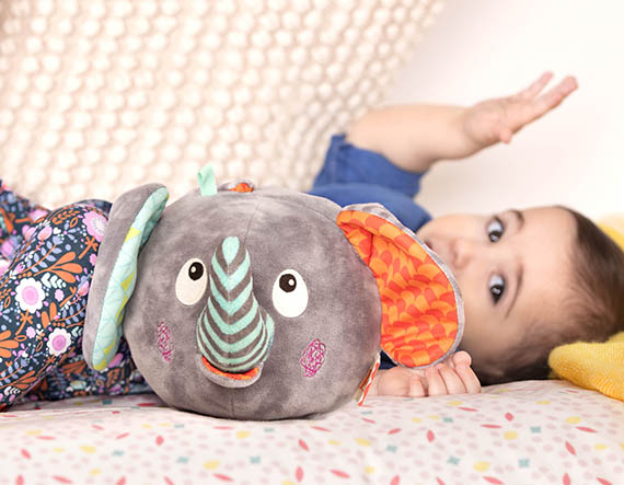 Baby with plush elephant toy.