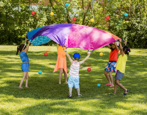 Kids with parachute outside.