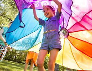 Smiling girl under a giant, colorful parachute.