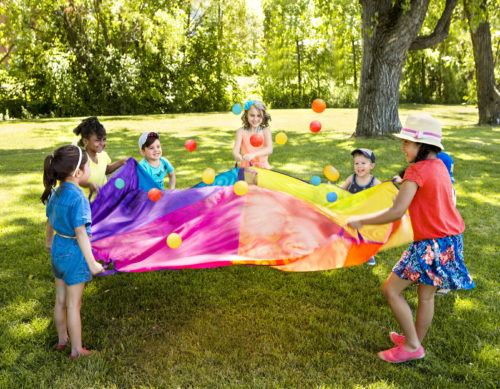 Kids playing with a parachute.