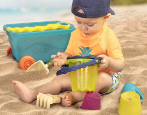 Boy sitting on the beach and playing with sand toys.