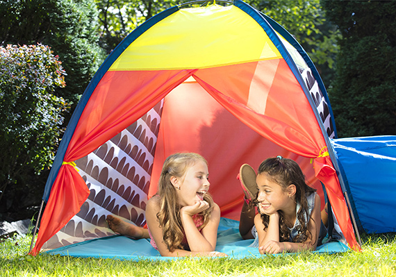 Two girls laughing in a tent outdoors.