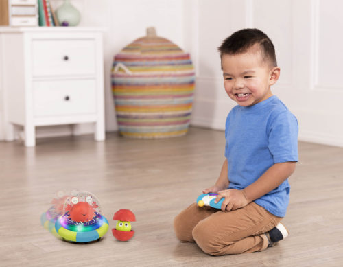 Smiling boy playing with an RC space ship.