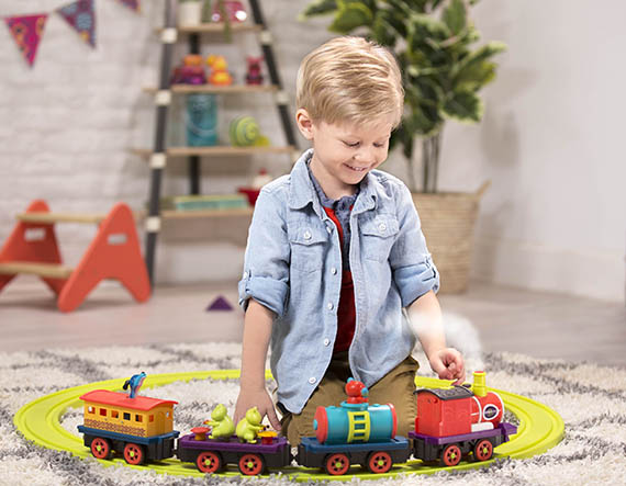 Smiling boy with train set.
