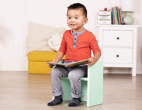 Toddler sitting on step stool.