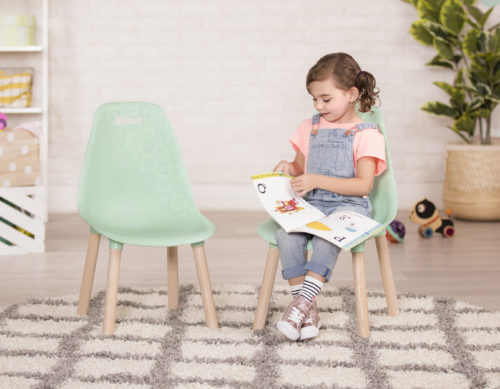 Girl reading a book on a chair.