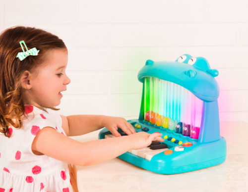 Girl playing on a hippo piano.