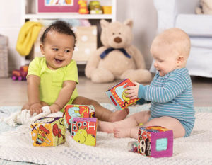Two smiling babies playing with blocks.