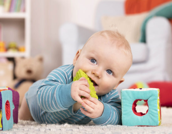 Smiling baby with toy blocks.