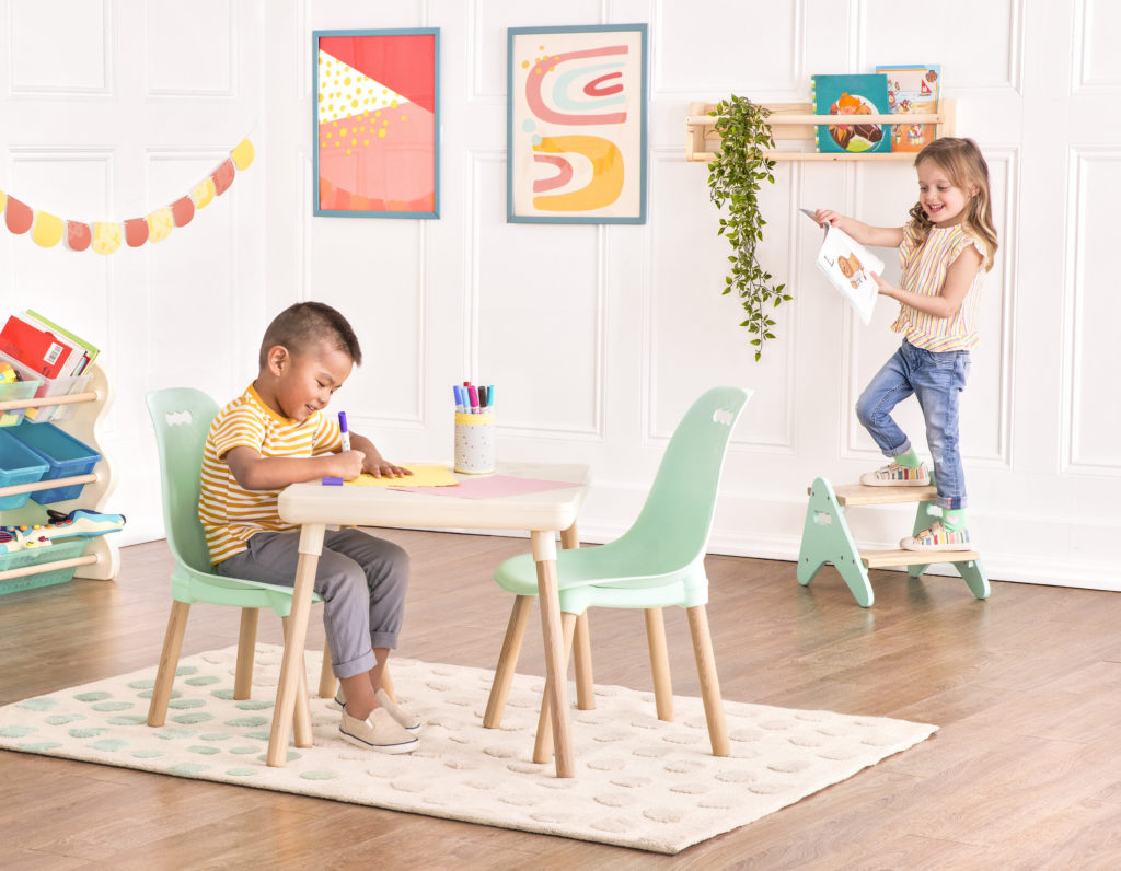 Smiling boy sitting at a kids table and drawing with markers and smiling girl holding a drawing while standing on a kids step stool.
