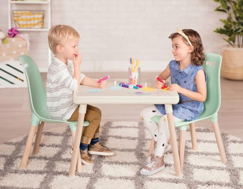 Two kids drawing at a kids table.