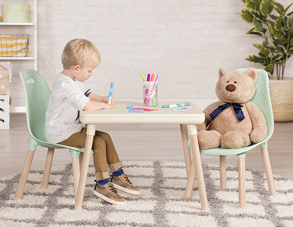 Boy sitting at a kids table with teddy bear across from him while drawing with markers.