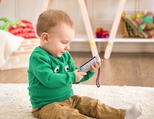 Baby with toy cell phone.