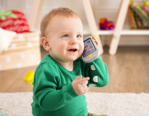 Smiling baby holding up a toy smartphone to their ear.