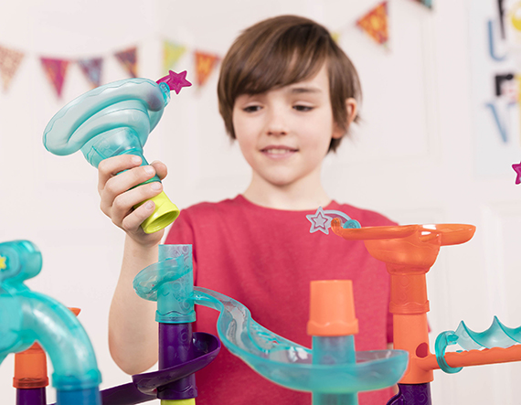 Boy holding a piece from a marble run toy.