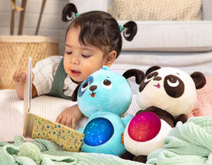 Baby girl reading a board book next to plush toys.