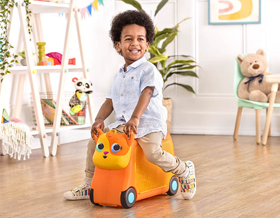 Smiling boy on ride-on cat suitcase.