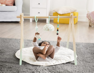 Baby in play gym with hanging toys.