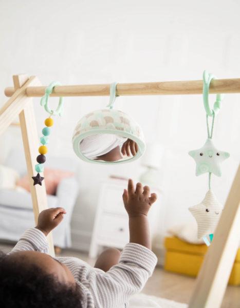 Baby reaching towards hanging toys.